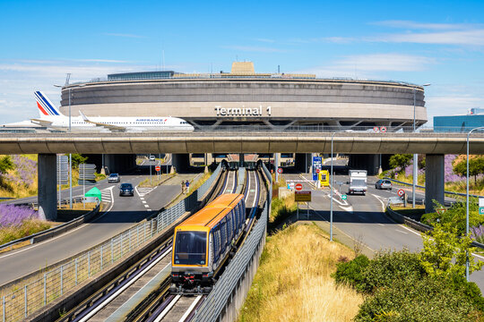 Roissy-en-France, France - July 27, 2020: View on the Terminal 1 of Paris-Charles de Gaulle Airport with an Air France airliner rolling on a taxiway bridge above the roads and airport shuttle line.