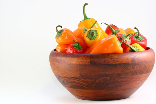 Red, yellow and orange mini peppers in a wooden bowl with copy space to the left
