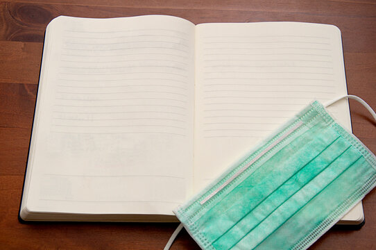 healthcare_hygienic mask_notebook_wooden background