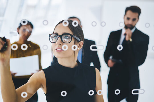 Charming caucasian woman leader in eyewear for vision correction spending time for training male and female employees writing information for startup project on modern board, concept of partnership