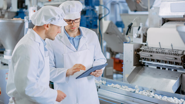 Two Young Male Quality Supervisors or Food Technicians are Inspecting the Automated Production at a Dumpling Food Factory. Employee Uses a Tablet Computer for Work. They Wear White Work Robes.