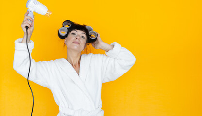 young beautiful woman housewife in a white robe. curlers on the head. Yellow background. blow dry hair