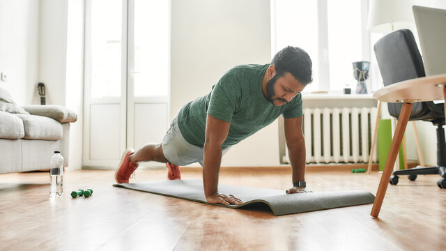 Online workout. Male fitness instructor showing push up exercises while streaming, broadcasting video lesson on training at home using laptop. Sport, online gym concept