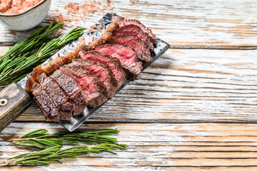 Grilled top sirloin cap or picanha steak on a meat cleaver with herbs. White wooden background. Top view. Copy space