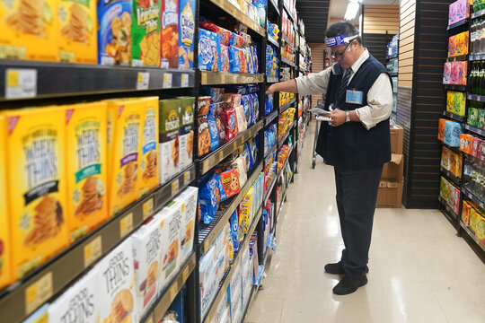 A worker with a face shield checks products on the shelf of a grocery store