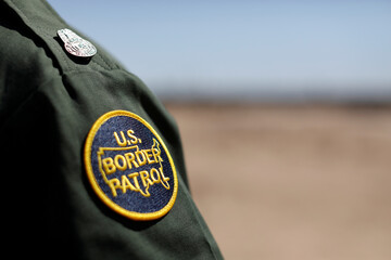 U.S. Customs and border patrol agent walks near the border wall in San Luis, Arizona