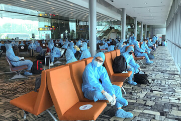 Vietnamese nationals wearing protective suits wait for boarding a repatriation flight from Singapore to Vietnam amid spread of the coronavirus disease (COVID-19) outbreak at Changi airport, Singapore