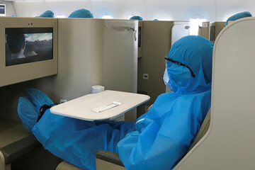 A Vietnamese national wearing protective suit is seen onboard before a repatriation flight from Singapore to Vietnam amid spread of the coronavirus disease (COVID-19) outbreak at Changi airport, Singapore