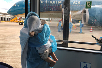 A Vietnamese woman wearing protective suit carries her child after their repatriation flight from Singapore landed amid spread of the coronavirus disease (COVID-19) outbreak at Can Tho airport