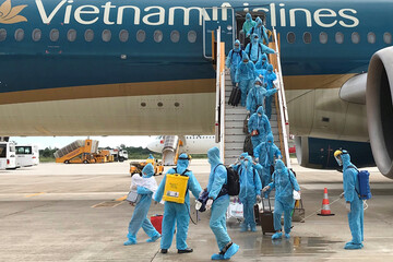 Healthcare workers spray disinfectant to Vietnamese nationals after their repatriation flight from Singapore landed amid spread of the coronavirus disease (COVID-19) outbreak at Can Tho airport