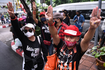 Pro-democracy protesters stand outside the criminal court building demanding a representative be allowed inside where two leaders are still detained at the criminal court in Bangkok