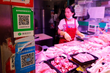 QR codes of the digital payment services WeChat Pay and its competitor Alipay are seen at a meat stall at a fresh market in Beijing
