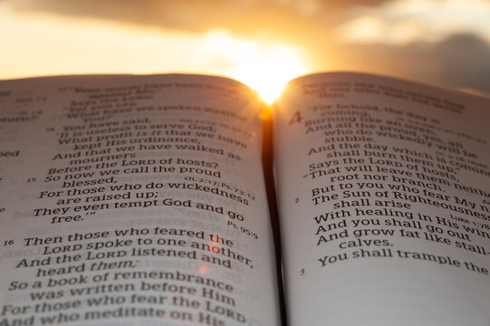 Holy Bible open at sunset with highlight on Malachi 4:2. Background with clouds and sun