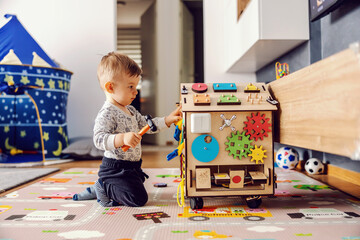 Obraz Adorable toddler playing interactive games for good development at home. - fototapety do salonu
