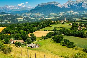 Top view of the bucolic fields with a wooden barn on the foreground and a typical french village and snowy Alps mountains on the background during summer season