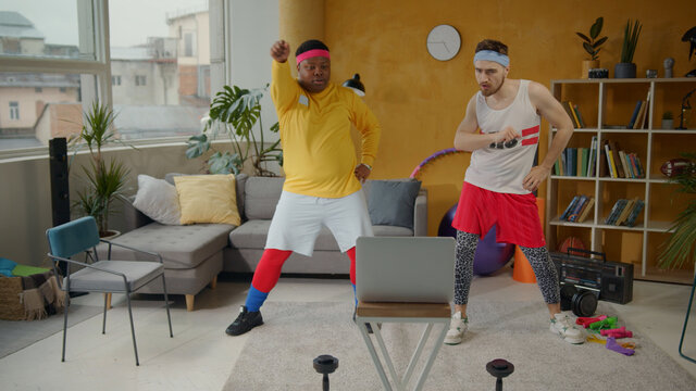 Joyful and funny retro style unfit sportsmen doing fun sports routine dancing with exercises into music during home training. Multi-ethnic fitness team.
