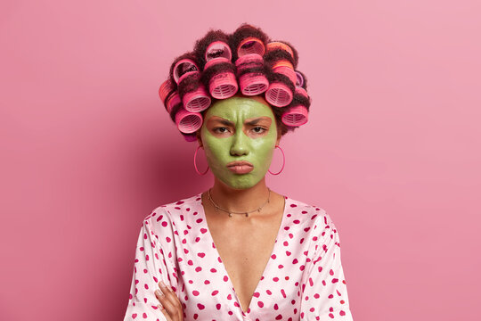 Offended displeased young woman applies beauty green face mask, tired of waiting for cosmetic product effect, wears curlers on hair, poses against rosy background. Housewife makes hairstyle.