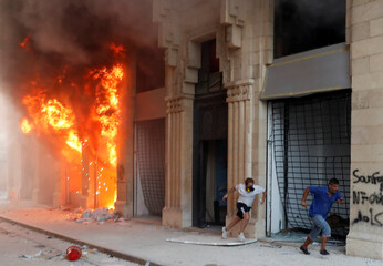 Protesters run away from security forces, in front of a burning building during a protest in Beirut
