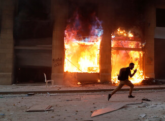 A protester runs away from security forces, in front of a burning building during a protest in Beirut