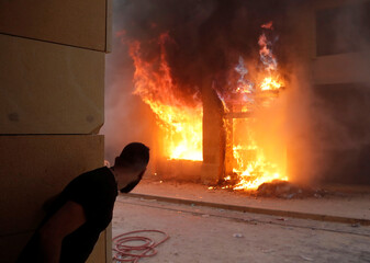 A demonstrator looks at Lebanese security forces, in front of a burning building during a protest in Beirut