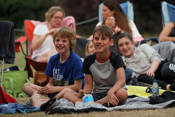 """Children watch the movie The Goonies at """"Sundown Cinema'"""" an outdoor cinema which began during the coronavirus disease (COVID-19) outbreak in a field in Ripley"""