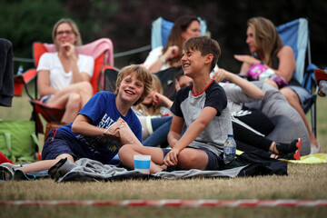 """Children watch the movie The Goonies at """"Sundown Cinema"""", an outdoor cinema which began during the coronavirus disease (COVID-19) outbreak, in a field in Ripley"""