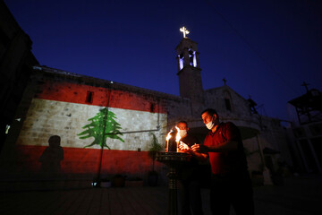 Christian worshippers light candles as they express their condolences to the Lebanese people, in Nazareth