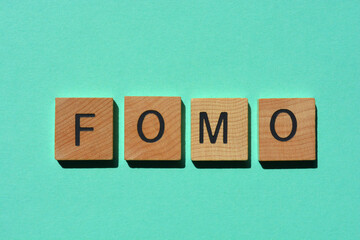 fomo, in acronym for Fear of Missing Out in wooden alphabet letters isolated on tyrquoise background