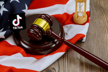 Conflict between the President of the United States and the Chinese company tik tok on Justice gavel lawyers office symbol legal law with hourglass on United States flag