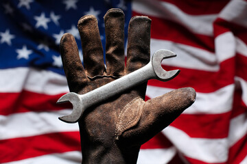 Hand in worn and dirty golve holding crescent wrench over American Flag