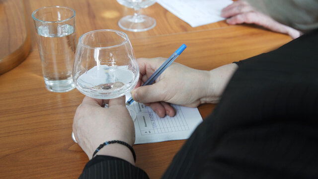 Female sommelier tasting alcohol drink in distillery. Woman is drinking vodka. Woman holding glass of vodka and taking notes. Evaluating color and degustation alcoholic beverages.