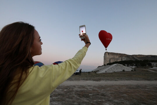 A spectator takes pictures during a hot air balloon competition in Crimea