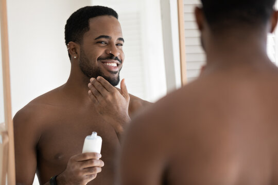 Mirror reflection close up smiling satisfied African American young man applying aftershave moisturizing lotion, standing in bathroom, enjoying skincare routine procedure after shaving
