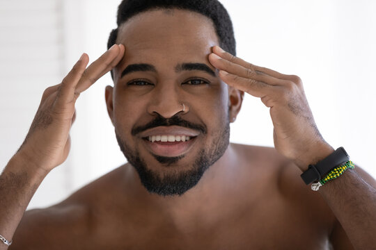 Head shot portrait smiling African American young man with naked shoulders checking wrinkles or acne on forehead, looking at camera, facial cosmetology, treatment, skincare concept