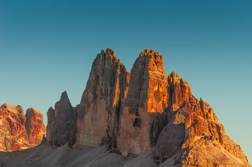 Beautiful sunset in magical Three Dolomite peaks at the national park Three Peaks (Tre Cime, Drei Zinnen) in Autumn colors at blue sky, South Tyrol, Italy, details