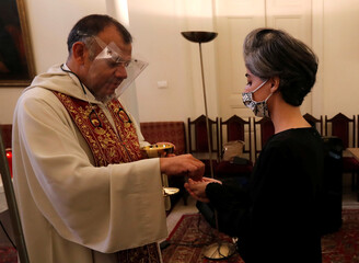 Woman receives Eucharist at church Sunday service following Tuesday's blast in Beirut