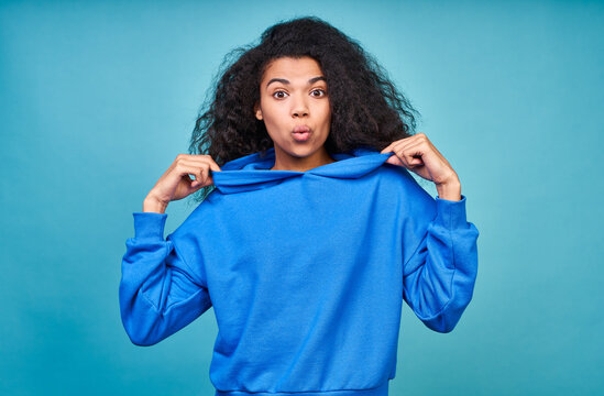 A funny teenage girl in a casual blue sweatshirt making grimaces.