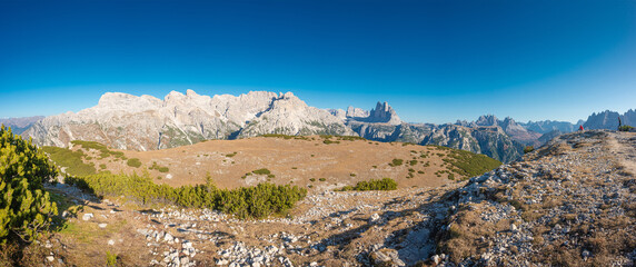 Panorama over beautiful sunset in Three Dolomite peaks at the national park Three Peaks (Tre Cime, Drei Zinnen) at sunny day, blue sky, seen from Strudelkopf summit, South Tyrol, Italy..