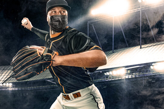 Porfessional baseball player in medical mask. Baseball game in 2020 - time of coronavirus pandemic. Ballplayer on stadium in action.