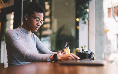 Pensive afro american photographer making notes analyzing ideas for earning money with vintage camera,businesswoman pondering on solving working problems sitting near copy space for advertising