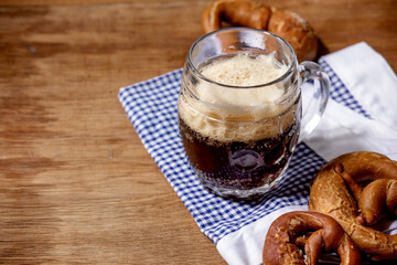 Glass of lager beer with traditional salted pretzels on white and blue napkin over wooden background. Oktoberfest theme