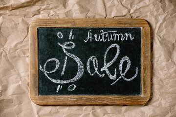 Autumn sale concept. Vintage chalkboard with hand written lettering Sale, labels with percents, yellow autumn leaves over craft crumpled paper. Flat lay.