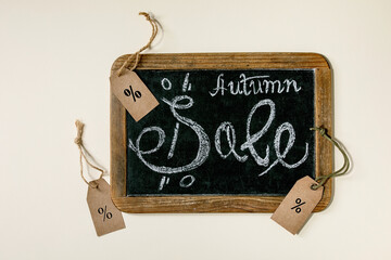 Autumn sale concept. Vintage chalkboard with hand written lettering Sale, labels with percents over beige background. Flat lay.