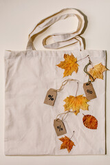 Autumn sale concept. Cardboard labels with percents, yellow autumn leaves on eco linen shopping bag over beige background. Flat lay.