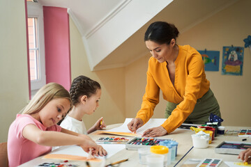 Beautiful woman helping children learn drawing in class room