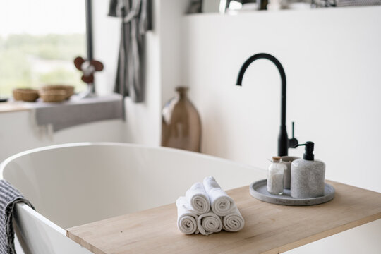 Towels on tub with modern black water tap at blurred background