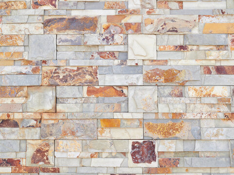 Background of rough natural stone brickwork wall in gray and brown colors with random patterns