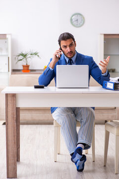 Young male employee working from house in self-isolation concept