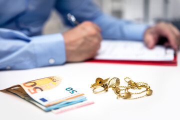 Businessman in the back, euro banknotes and gold jewellry in the front