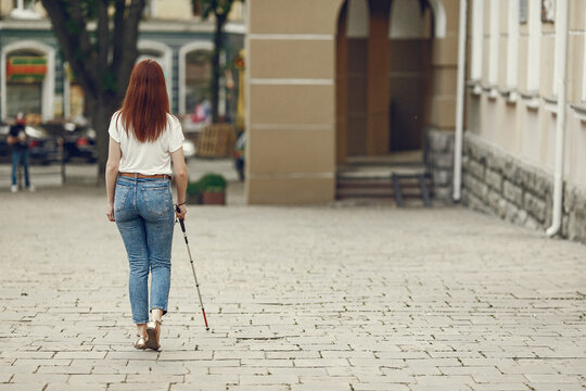 Blind woman is walking on the sidewalk in city. Woman using a white cane.